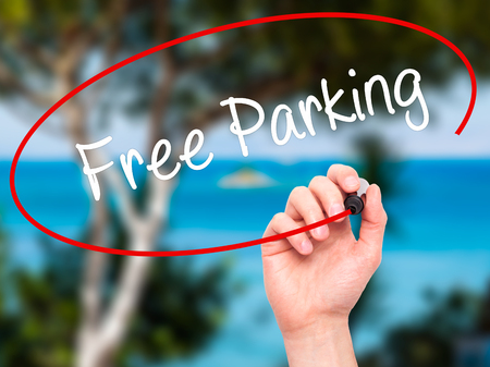 visual screen: Man Hand writing Free Parking with black marker on visual screen. Isolated on nature. Business, technology, internet concept. Stock Photo
