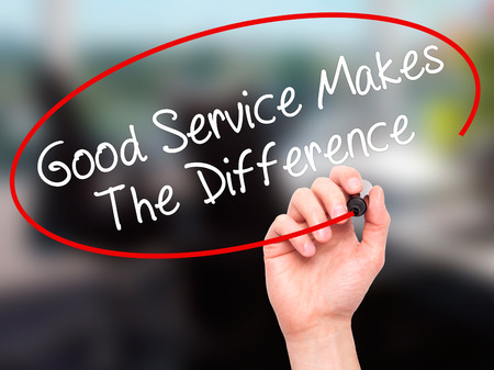 Man Hand writing Good Service Makes The Difference with black marker on visual screen. Isolated on office. Business, technology, internet concept. Stock Photo Standard-Bild