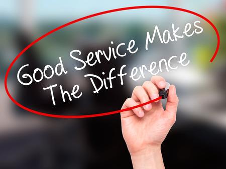 Man Main écrire un bon service fait la différence avec un marqueur noir sur l'écran visuel. Isolé sur le bureau. Affaires, technologie, internet concept. photo