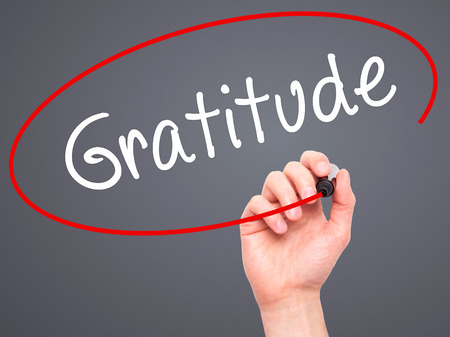 thankfulness: Man Hand writing Gratitude with black marker on visual screen. Isolated on grey. Business, technology, internet concept. Stock Photo