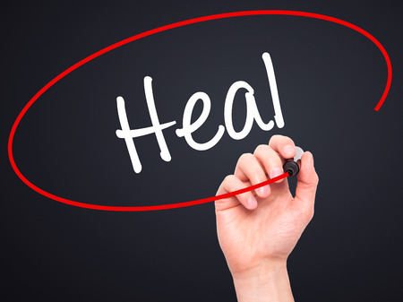 resonate: Man Hand writing  Heal  with black marker on visual screen. Isolated on background. Business, technology, internet concept. Stock Photo Stock Photo