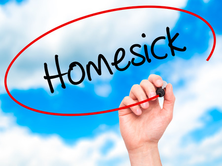 hankering: Man Hand writing Homesick with black marker on visual screen. Isolated on sky. Business,  internet concept. Stock Photo