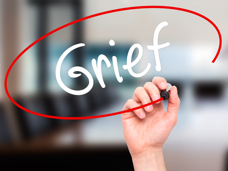 dolor: Man Hand writing Grief with black marker on visual screen. Isolated on background. Business, technology, internet concept. Stock Photo