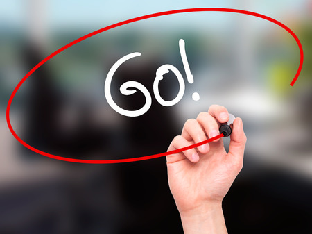 working ethic: Man Hand writing Go! with black marker on visual screen. Isolated on office. Business, technology, internet concept. Stock Photo Stock Photo