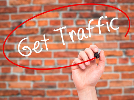 pageviews: Man Hand writing Get Traffic with black marker on visual screen. Isolated on bricks. Business, technology, internet concept. Stock Photo