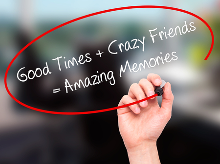 Man Hand writing Good Times + Crazy Friends = Amazing Memories with black marker on visual screen. Isolated on background. Business, technology, internet concept. Stock Photo
