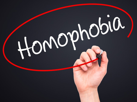 homophobia: Man Hand writing Homophobia with black marker on visual screen. Isolated on background. Business, technology, internet concept. Stock Photo