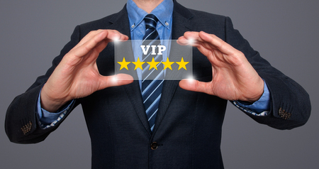 hotel reviews: Businessman holding five star rating VIP - Grey - Stock Image Stock Photo