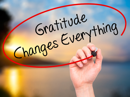 Man Hand writing Gratitude Changes Everything with black marker on visual screen. Isolated on nature. Business, technology, internet concept. Stock Photo