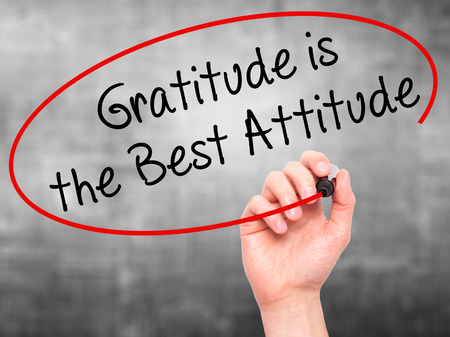 agradecimiento: Man Hand writing Gratitude is the Best Attitude with black marker on visual screen. Isolated on grey. Business, technology, internet concept. Stock Photo Foto de archivo