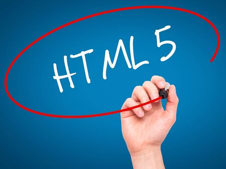 html 5: Man Hand writing HTML 5 with black marker on visual screen. Isolated on blue. Business, technology, internet concept. Stock Photo