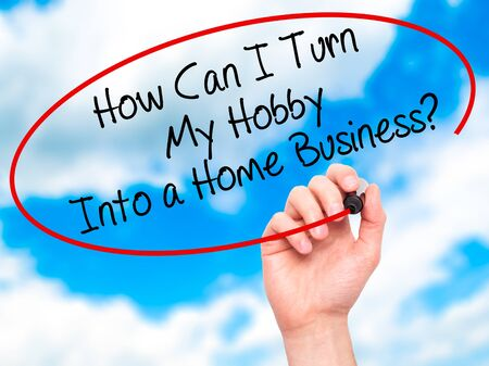 self discovery: Man Hand writing How Can I Turn My Hobby Into a Home Business? with black marker on visual screen. Isolated on background. Business, technology, internet concept. Stock Photo Stock Photo