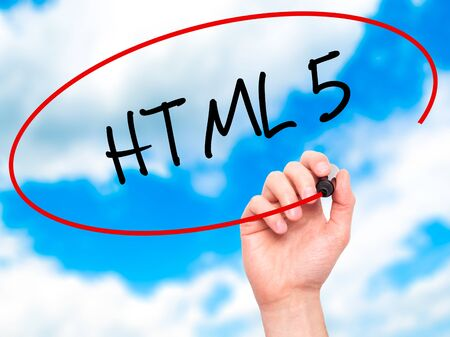 html 5: Man Hand writing HTML 5 with black marker on visual screen. Isolated on sky. Business, technology, internet concept. Stock Photo