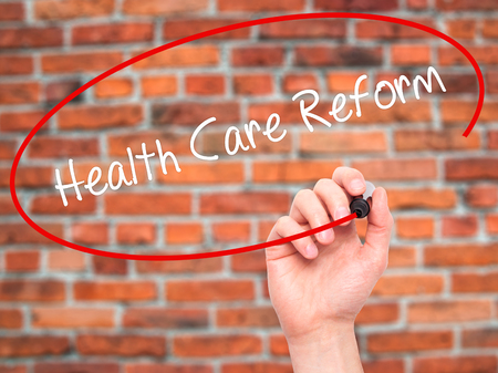 obama care: Man Hand writing Health Care Reform with black marker on visual screen. Isolated on bricks. Business, technology, internet concept.