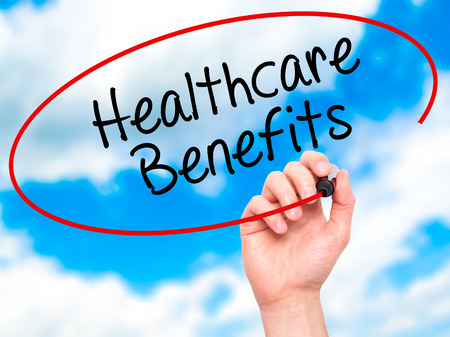 medicaid: Man Hand writing Healthcare Benefits with black marker on visual screen. Isolated on sky. Business, technology, internet concept. Stock Photo