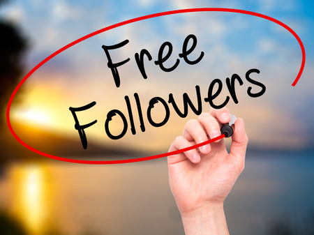 free me: Man Hand writing Free Followers with black marker on visual screen. Isolated on nature. Business, technology, internet concept. Stock Photo