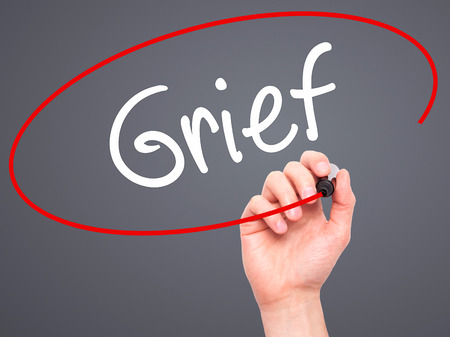 bother: Man Hand writing Grief with black marker on visual screen. Isolated on background. Business, technology, internet concept. Stock Photo