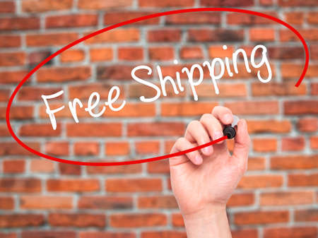 writing on screen: Man Hand writing Free Shipping with black marker on visual screen. Isolated on bricks. Business, technology, internet concept. Stock Photo Stock Photo