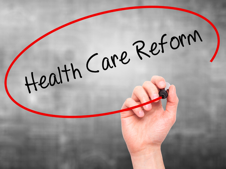 obama care: Man Hand writing Health Care Reform with black marker on visual screen. Isolated on grey. Business, technology, internet concept.