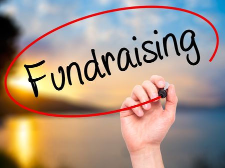 fundraising: Man Hand writing Fundraising with black marker on visual screen. Isolated on background. Business, technology, internet concept. Stock Photo