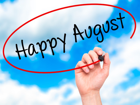 august: Man Hand writing Happy August with black marker on visual screen. Isolated on sky. Business, technology, internet concept. Stock Photo
