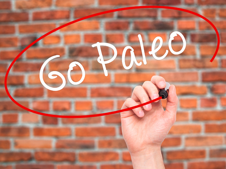 free background: Man Hand writing Go Paleo with black marker on visual screen. Isolated on bricks. Business, technology, internet concept. Stock Photo