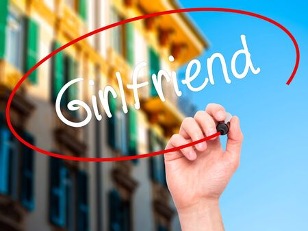 severance: Man Hand writing Girlfriend with black marker on visual screen. Isolated on city. Business, technology, internet concept.