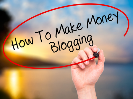 monetization: Man Hand writing How To Make Money Blogging with black marker on visual screen. Isolated on nature. Business, technology, internet concept. Stock Photo Stock Photo