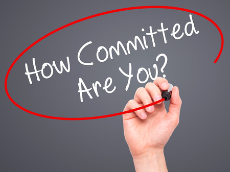 committed: Man Hand writing How Committed Are You? with black marker on visual screen. Isolated on grey. Business, technology, internet concept. Stock Photo Stock Photo