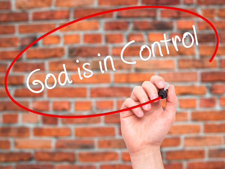 confessing: Man Hand writing God is in Control with black marker on visual screen. Isolated on bricks. Business, technology, internet concept. Stock Photo