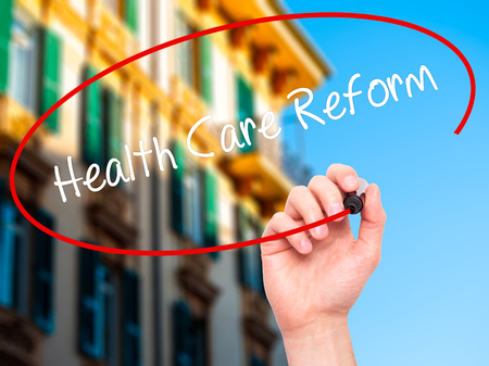 Man Hand writing Health Care Reform with black marker on visual screen. Isolated on city. Business, technology, internet concept.