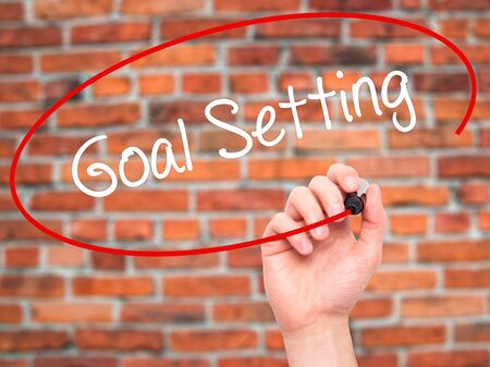 Man Hand writing Goal Setting  with black marker on visual screen. Isolated on bricks. Business, technology, internet concept. Stock Photo