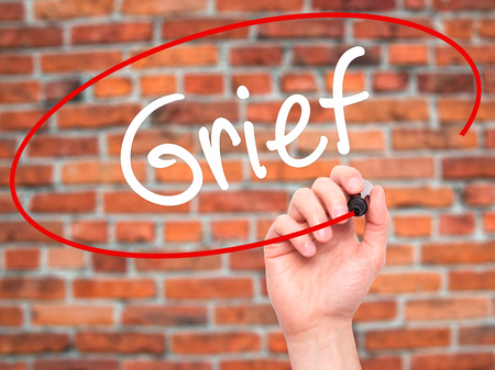 Man Hand writing Grief with black marker on visual screen. Isolated on background. Business, technology, internet concept. Stock Photo