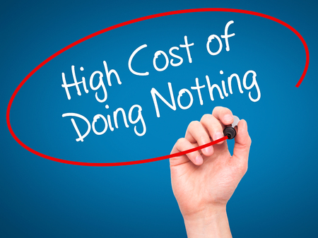 high cost: Man Hand writing High Cost of Doing Nothing with black marker on visual screen. Isolated on blue. Business, technology, internet concept. Stock Photo