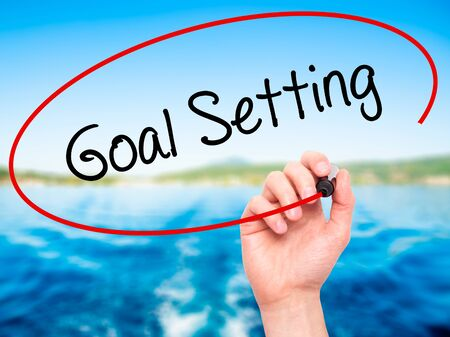 Man Hand writing Goal Setting  with black marker on visual screen. Isolated on nature. Business, technology, internet concept. Stock Photo Stock Photo