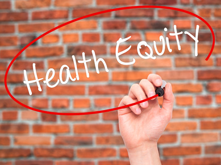 health equity: Man Hand writing Health Equityt with black marker on visual screen. Isolated on bricks. Business, technology, internet concept. Stock Photo Stock Photo