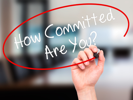 committed: Man Hand writing How Committed Are You? with black marker on visual screen. Isolated on office. Business, technology, internet concept. Stock Photo