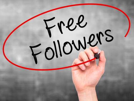 followers: Man Hand writing Free Followers with black marker on visual screen. Isolated on grey. Business, technology, internet concept. Stock Photo
