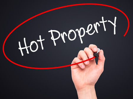 Man Hand writing Hot Property with black marker on visual screen. Isolated on black. Business, technology, internet concept. Stock Photo