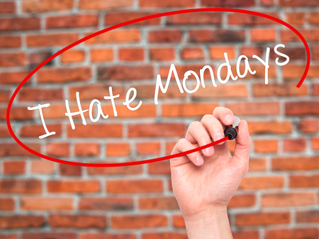 Man Hand writing I Hate Mondays with black marker on visual screen. Isolated on background. Business, technology, internet concept. Stock Photo