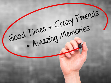 Man Hand writing Good Times + Crazy Friends = Amazing Memories with black marker on visual screen. Isolated on background. Business, technology, internet concept. Stock Photo Stock Photo