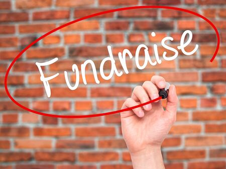 Man Hand writing Fundraise with black marker on visual screen. Isolated on background. Business, technology, internet concept. Stock Photo
