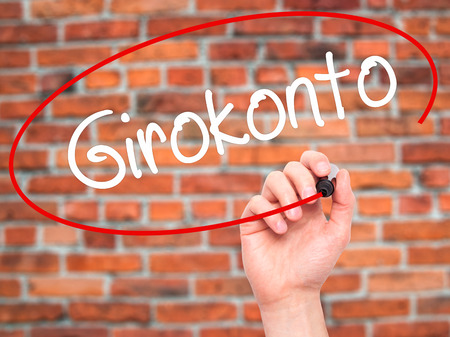 checking account: Man Hand writing  Girokonto (Checking Account) with black marker on visual screen. Isolated on background. Business, technology, internet concept. Stock Photo Stock Photo