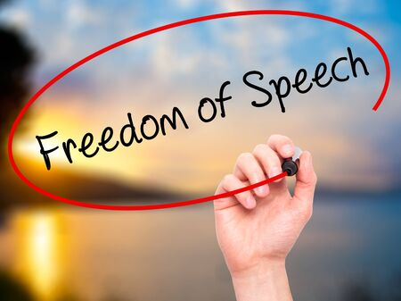 censure: Man Hand writing Freedom of Speech with black marker on visual screen. Isolated on nature. Business, technology, internet concept. Stock Photo Stock Photo