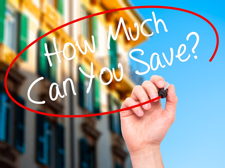 mortgaging: Man Hand writing How Much Can You Save? with black marker on visual screen. Isolated on city. Business, technology, internet concept. Stock Photo