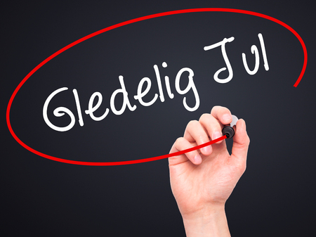 december 25th: Man Hand writing Gledelig Jul  (Happy Christmas in Norwegian) with black marker on visual screen. Isolated on background. Business, technology, internet concept. Stock Photo