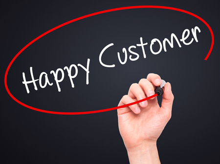 cause marketing: Man Hand writing Happy Customer with black marker on visual screen. Isolated on black. Business, technology, internet concept. Stock Photo