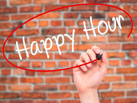 happyhour: Man Hand writing Happy Hour with black marker on visual screen. Isolated on bricks. Business, technology, internet concept. Stock Image