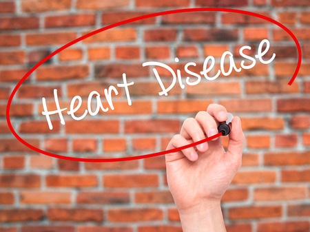 arrhythmias: Man Hand writing Heart Disease with black marker on visual screen. Isolated on bricks. Business, technology, internet concept. Stock Photo