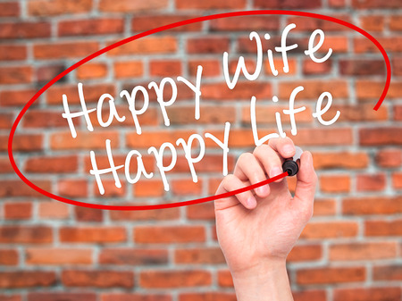 wedlock: Man Hand writing Happy Wife Happy Life with black marker on visual screen. Isolated on bricks. Business, technology, internet concept. Stock Photo